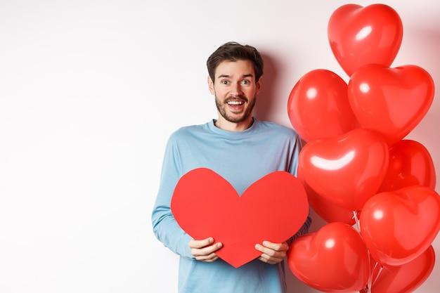 Glimlachend vriendje houdt valentijnskaart vast en staat in de buurt van romantische rode hartballonnen, viert de dag van geliefden, staande op een witte achtergrond.