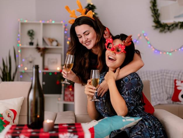 Glimlachend vrij jong meisje met rendieren hoofdband houdt glas champagne en hugs haar vriend met rendieren bril zittend op een fauteuil en genieten van kersttijd thuis