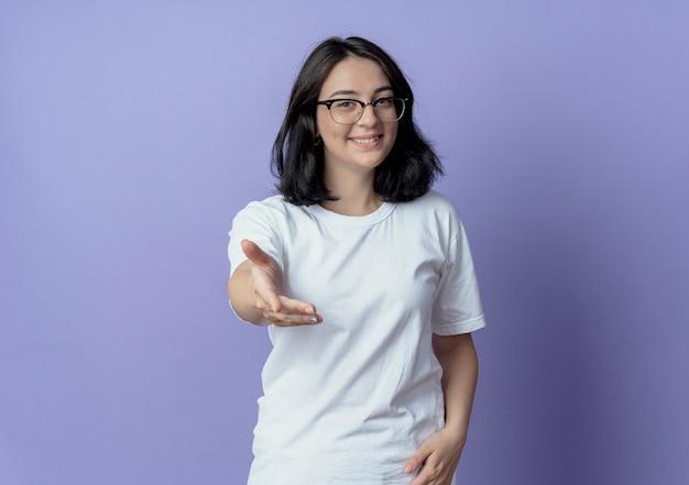 Glimlachend vrij kaukasisch meisje dat glazen draagt die uit hand bij camera uitrekt die op purpere achtergrond met exemplaarruimte wordt geïsoleerd