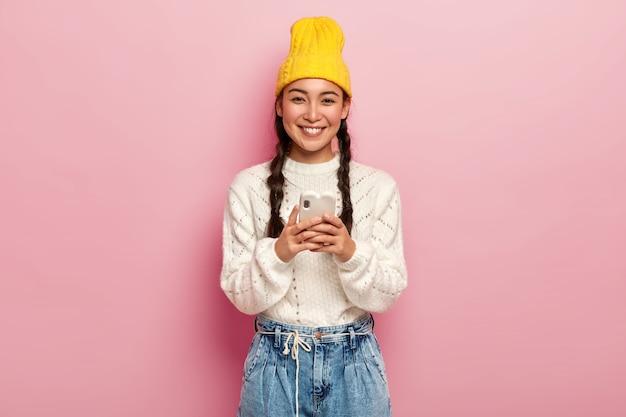 Glimlachend vrij millennial meisje moderne mobiele telefoon gebruikt, verbonden met draadloos internet, afbeeldingen downloadt, e-mailbox controleert, draagt gele hoed