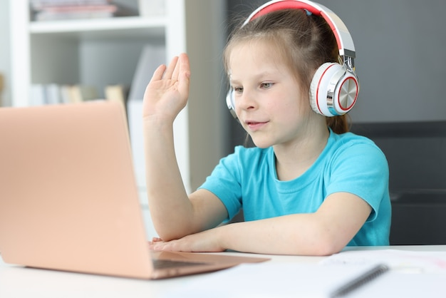Glimlachend vrij schattig klein jaar oud meisje in koptelefoon kijken naar laptop scherm