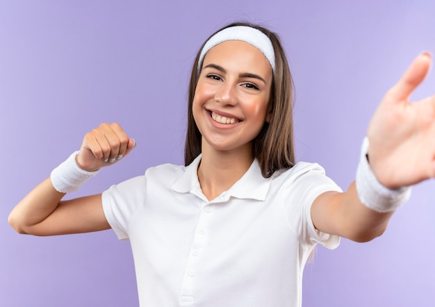 Glimlachend vrij sportief meisje dat hoofdband en polsbandje draagt dat uit hand met gebalde vuist uitrekt die op purpere ruimte wordt geïsoleerd