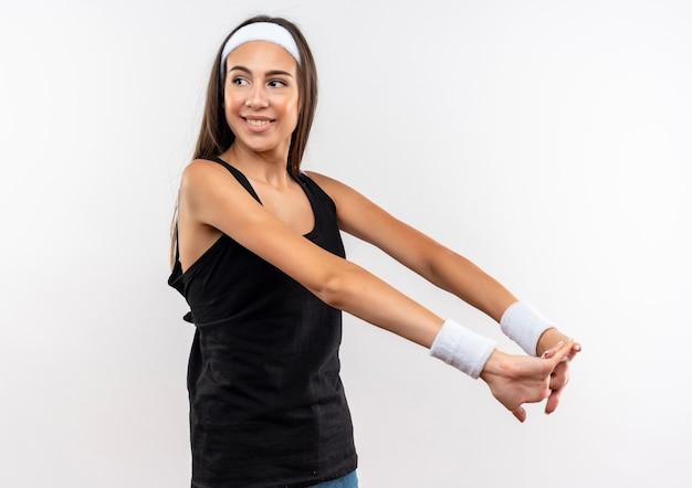 Glimlachend vrij sportief meisje die hoofdband en polsband dragen die handen samen houden die kant bekijken die op witte ruimte wordt geïsoleerd