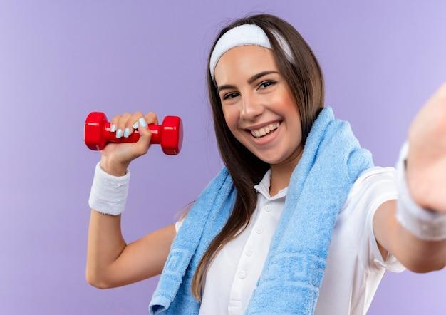 Glimlachend vrij sportief meisje die hoofdband en polsbandje dragen die halter met handdoek om hals houden die op purpere ruimte wordt geïsoleerd