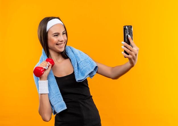 Glimlachend vrij sportief meisje dragen hoofdband en polsbandje houden en kijken naar mobiele telefoon en halter met handdoek om haar nek geïsoleerd op oranje ruimte te houden