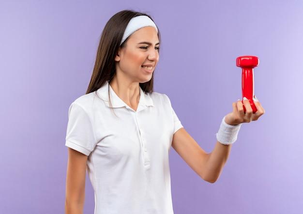 Glimlachend vrij sportief meisje met hoofdband en polsbandje houden en kijken naar het geïsoleerd op paarse ruimte