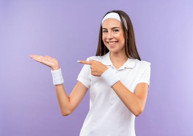 Glimlachend vrij sportief meisje met hoofdband en polsbandje met lege hand en wijzend op het geïsoleerd op paarse ruimte