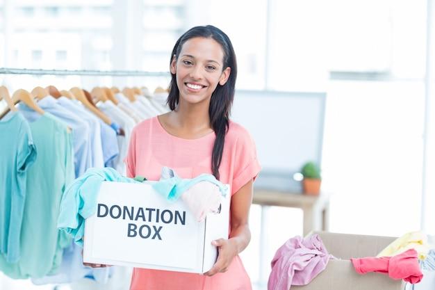 Glimlachend vrijwilliger met een doos met donaties