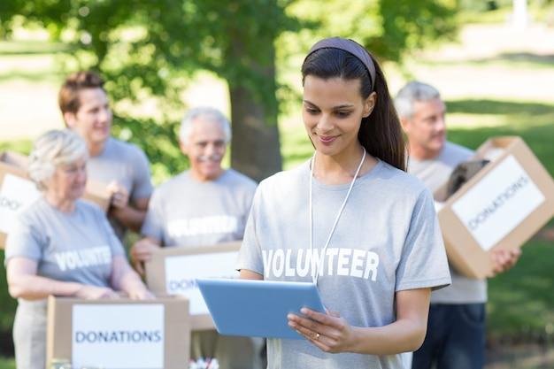 Glimlachend vrijwilligersbrunette die tabletpc met behulp van