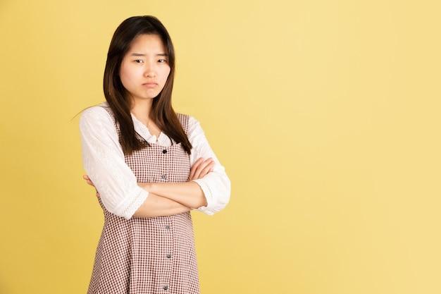 Glimlachend, vrolijk. het portret van de aziatische jonge vrouw op gele muur. mooi vrouwelijk model in casual stijl. concept van menselijke emoties, gezichtsuitdrukking, jeugd, verkoop, advertentie.