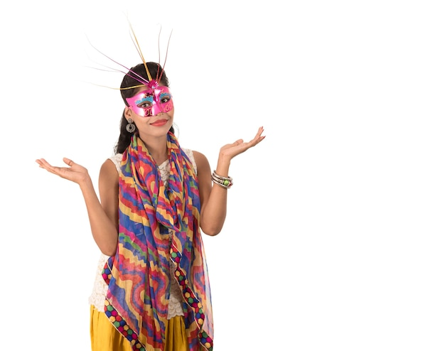 Glimlachend vrolijk meisje dat carnaval-masker draagt en teken toont dat op witte achtergrond wordt geïsoleerd