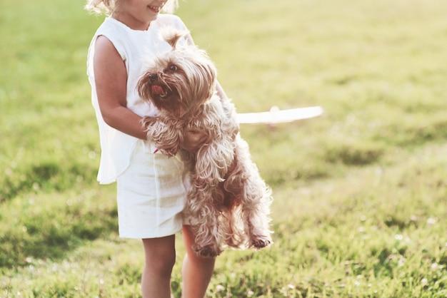 Glimlachend vrolijk meisje dat hondje vasthoudt en met hem buiten in het veld speelt playing
