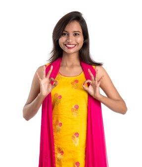 Glimlachend vrolijk meisje dat teken toont dat op witte achtergrond wordt geïsoleerd