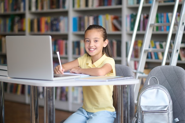 Glimlachend vrolijk meisje opschrijven in haar notitieboekje
