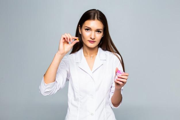 Glimlachend vrouwelijk de pillenmedicijn van de artsenholding dat op een witte muur wordt geïsoleerd.