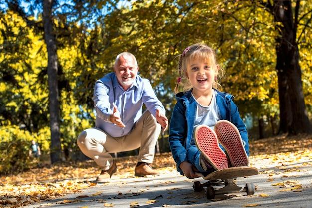 Glimlachend vrouwelijk kleinkind speelt met haar grootvader in het park