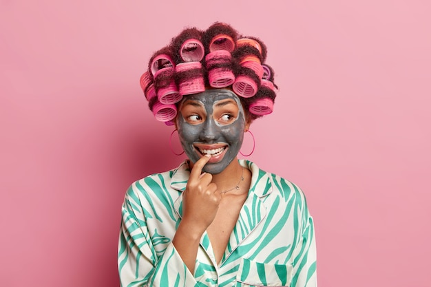 Glimlachend vrouwelijk model houdt wijsvinger in de buurt van tanden zorgt voor haar teint past schoonheid kleimasker maakt kapsel gekleed in huishoudelijke kleding geïsoleerd over roze muur. cosmetologie