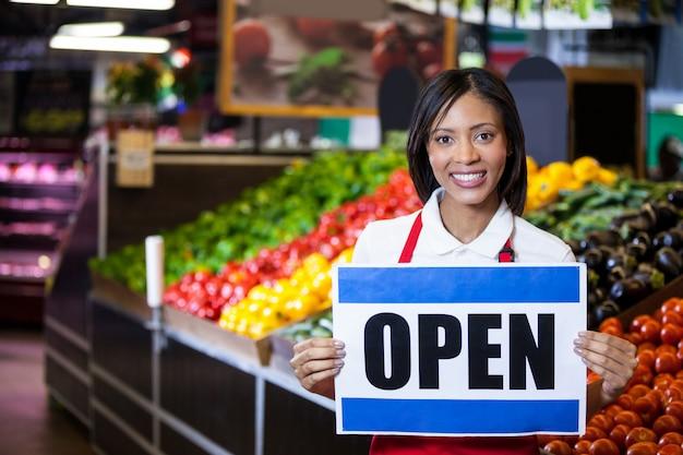 Glimlachend vrouwelijk personeel dat open uithangbord houdt