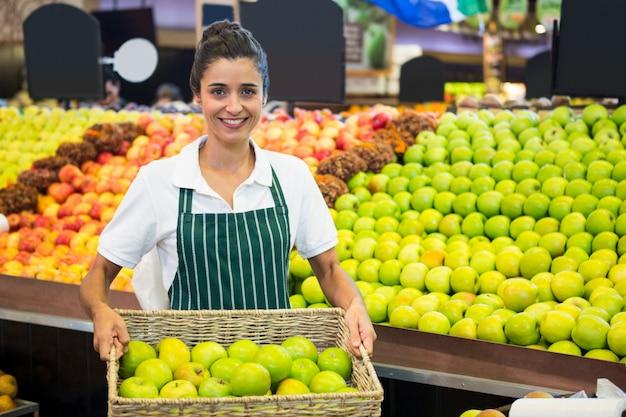 Glimlachend vrouwelijk personeel die een mand groene appel houden bij supermarkt
