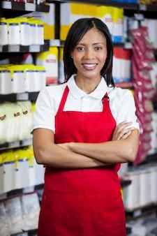 Glimlachend vrouwelijk personeel die zich met die wapens bevinden in kruidenierswinkelsectie worden gekruist
