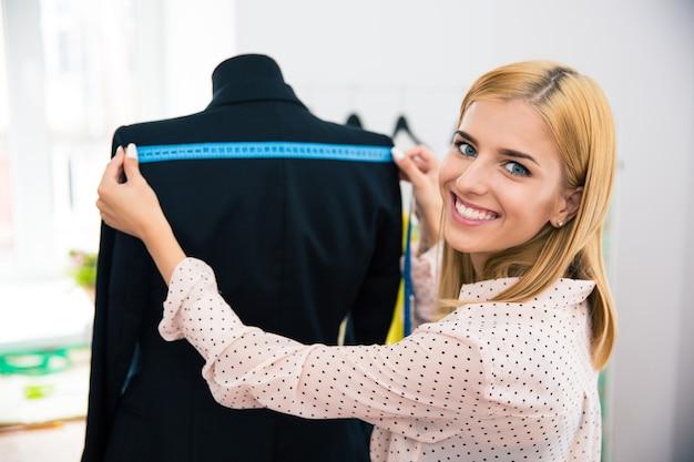 Glimlachend vrouwelijke kleermaker meetlint jasje