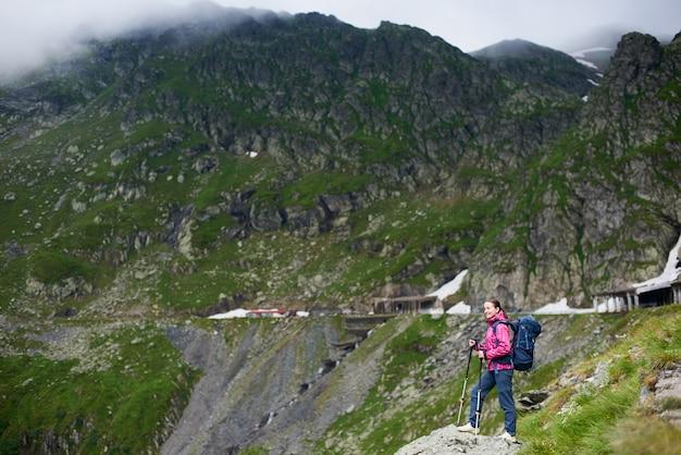 Glimlachend wandelaarmeisje met blauwe rugzak en trekkingstokken die zich in een vallei onder rotsachtige bergen bevinden
