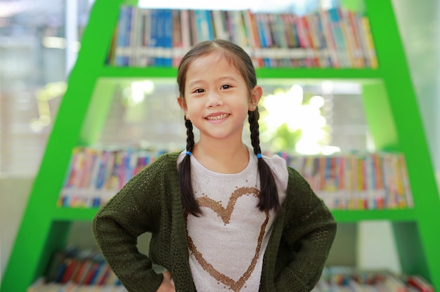 Glimlachend weinig aziatisch kindmeisje tegen boekenrek bij bibliothecaris