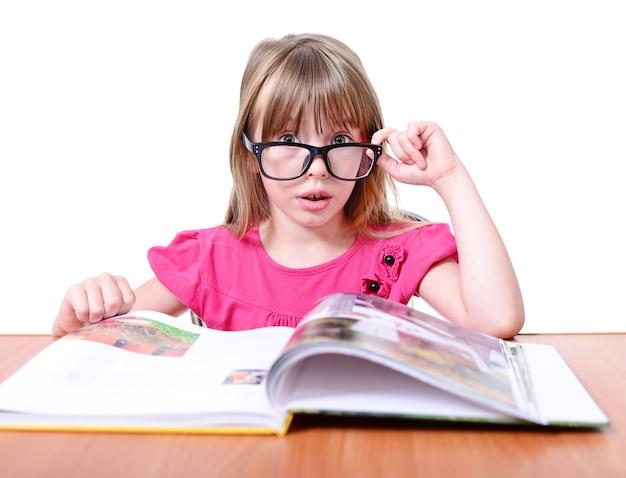 Glimlachend weinig schoolmeisje met boek dat op wit wordt geïsoleerd.