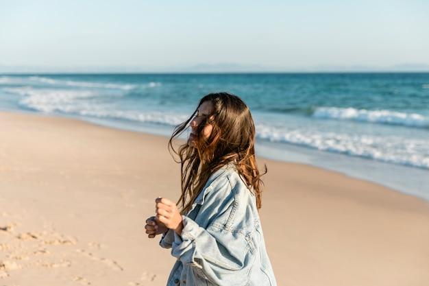 Glimlachend wijfje dat op kust in zonneschijn lacht