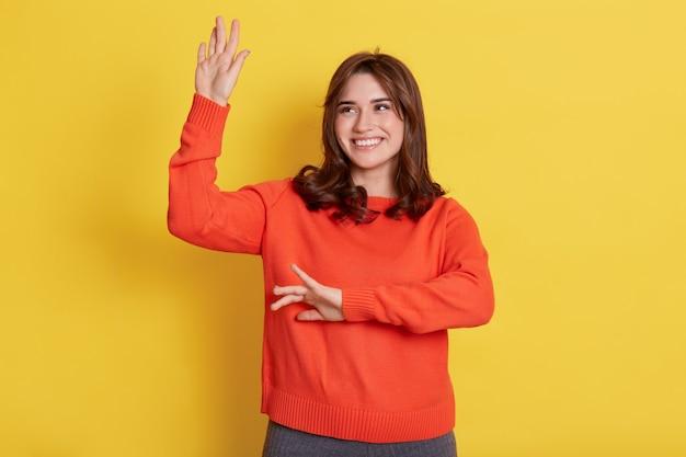 Glimlachend wijfje met gelukkige gezichtsuitdrukking die dromerig opzij kijkt, handen opheft en danst, haar succes viert, poseren geïsoleerd over gele muur.