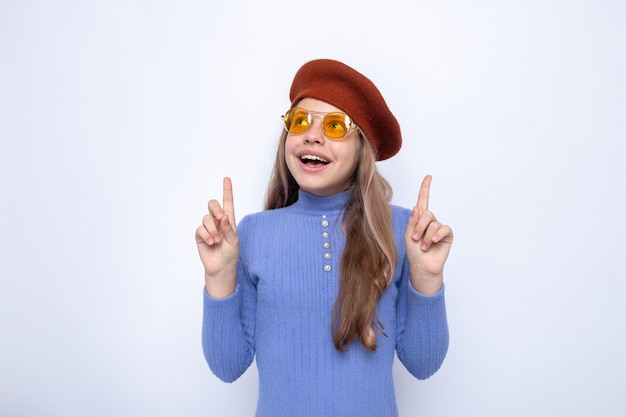 Glimlachend wijst naar een mooi klein meisje met een bril met hoed