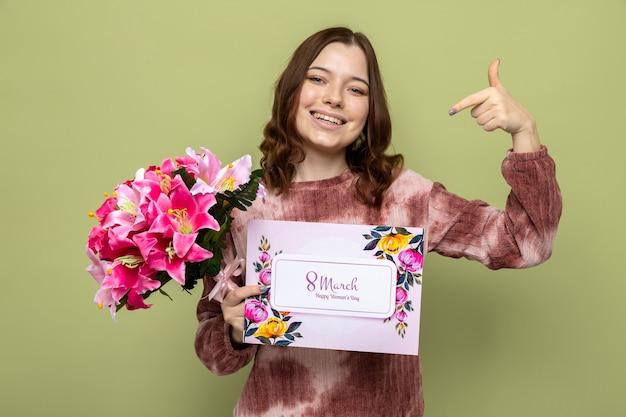 Glimlachend wijst naar zichzelf, mooi jong meisje op een gelukkige vrouwendag met boeket met ansichtkaart geïsoleerd op olijfgroene muur