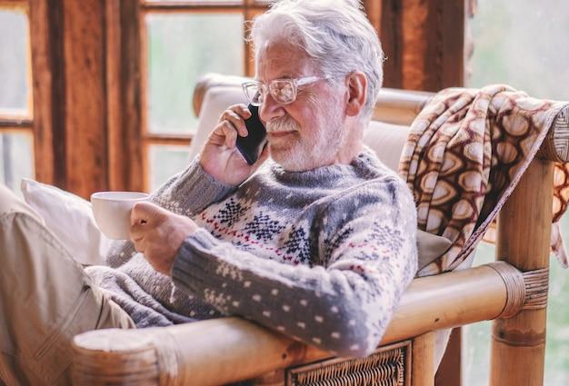 Glimlachend witharige senior man in winter trui zittend in de woonkamer met een kopje thee met behulp van mobiele telefoon zorgeloos bejaarde grootvader genieten van tech en sociaal. rustiek chalet in het bos