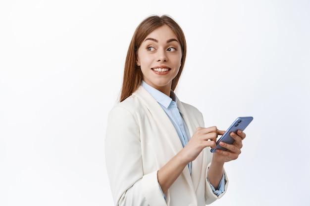 Glimlachend zakelijk meisje in pak met mobiele telefoon, hoofd naar achteren draaien en naar promotionele tekst kijken, kopieerruimte op witte muur lezen, smartphone vasthouden