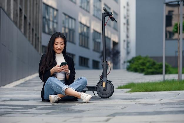Glimlachend zelfverzekerd aziatisch meisje dat op het asfalt dichtbij elektrische autoped rust