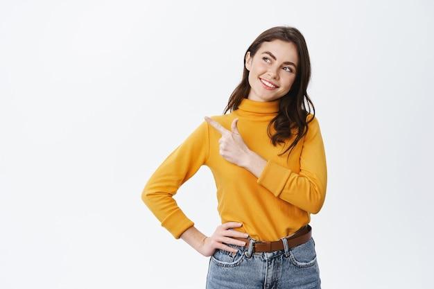 Glimlachend zelfverzekerd meisje kijkend en wijzend naar links naar promo-aanbieding, starend met tevreden vastberaden gezicht naar advertentie, keuze makend, staande op een witte muur