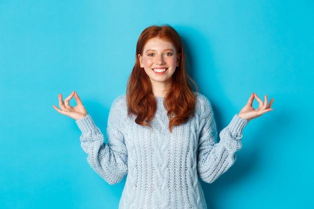 Glimlachend zelfverzekerd meisje met rood haar dat geduldig blijft, handen vasthoudt in zen, meditatie pose en naar de camera staart, yoga beoefent, kalm staat tegen een blauwe achtergrond.
