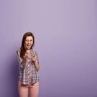 Glimlachend zelfverzekerd vrouwelijk model wijst beide vingers, maakt ondersteunend gebaar, moedigt je aan om lid te worden van het team, knippert met de ogen, draagt een casual shirt en een roze broek, zegt dat je de volgende bent