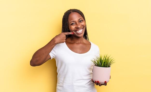 Glimlachend zelfverzekerd wijzend naar eigen brede glimlach, positieve, ontspannen, tevreden houding met een plantenpot