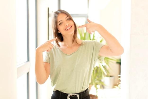 Glimlachend zelfverzekerd wijzend naar eigen brede glimlach, positieve, ontspannen, tevreden houding