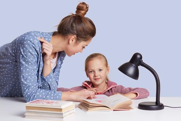 Glimlachend zit weinig charmant meisje bij lijst en haar moeder helpt haar om huiswerkopdracht te doen, samen gedicht proberen te leren, gebruikt leeslamp voor goede visie, die op wit wordt geïsoleerd.