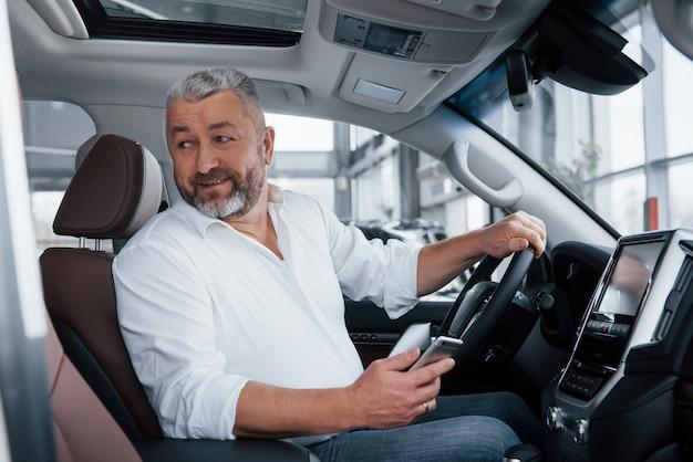Glimlachend zittend in een gloednieuwe auto. senior bebaarde man in wit overhemd houdt mobiele telefoon
