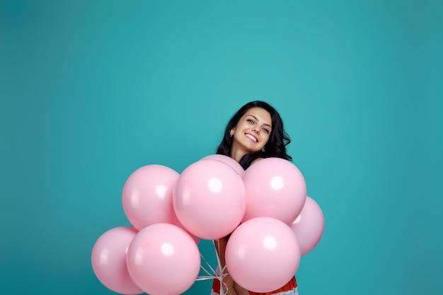 Glimlachend zorgeloos krullend meisje in jurk met pastel roze lucht ballonnen geïsoleerd op blauwe achtergrond. gelukkige jonge vrouw op een verjaardagsfeestje. geluk. ruimte voor tekst