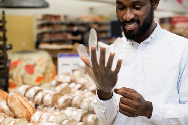 Glimlachend zwart mannetje die handschoen op bij kruidenierswinkelopslag zetten om brood te kopen