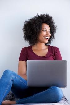 Glimlachend zwarte thuis ontspannen met laptopcomputer