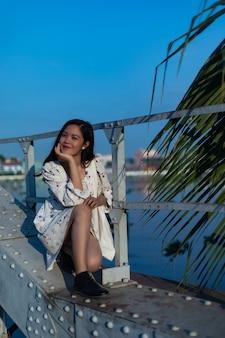 Glimlachend zwartharige vietnamees meisje, zittend op een brug