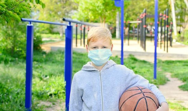 Glimlachende 9-jarige jongen op straat deed zijn medisch masker af en speelt de bal. einde van zelfisolatie. corona-epidemie.