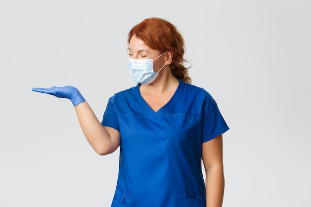 Glimlachende aangename vrouwelijke arts, verpleegster die gelukkig kijkt alsof hij iets bij de hand houdt, gezichtsmasker en rubberen handschoenen draagt