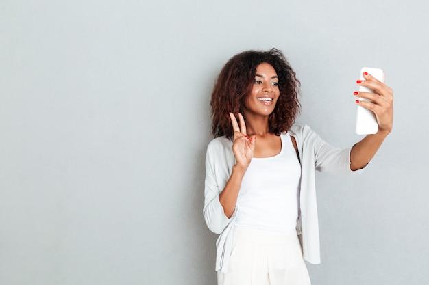 Glimlachende aantrekkelijke afrikaanse vrouw die een selfie neemt