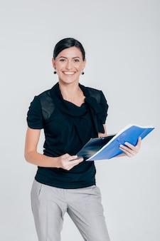 Glimlachende aantrekkelijke bedrijfsvrouw die een omslag met documenten op een grijze achtergrond houdt
